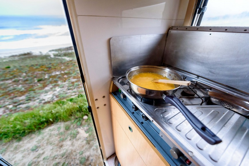 Cooking in campervan by the beach