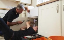 Plumber teaching a young apprentice to fix a kitchen sink 000074342145 Double copy2